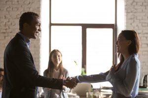 Man overhandigt een visitekaartje aan zakenvrouw